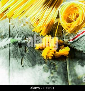 Assortiment de pâtes italiennes séchées allongé sur old weathered planches en bois avec des spaghetti, fusilli, Banque D'Images