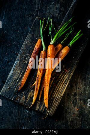 Des tas de jeunes carottes frites tout prêt à être mangé servi sur une vieille planche de bois rustique grungy, Banque D'Images