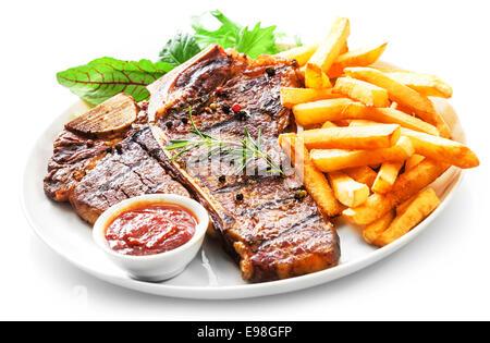 L'aloyau grillé tendre ou t-bone steak servi avec des frites dorées et salade d'herbes fraîches accompagnées d'un Banque D'Images