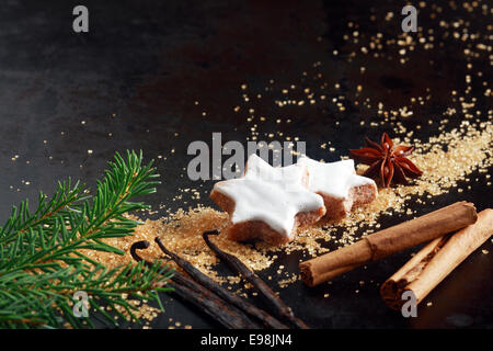 Épicé croquant des biscuits de Noël en forme d'étoile vitrage avec glaçage blanc disposés sur un fond sombre avec Banque D'Images
