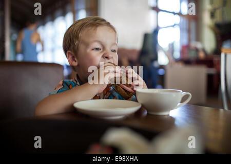 Petit garçon dans un café sandwich ayant Banque D'Images