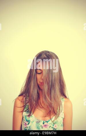 Portrait d'une jeune femme brune avec ses cheveux dans son visage et ses yeux fermés, avec un effet rétro Banque D'Images