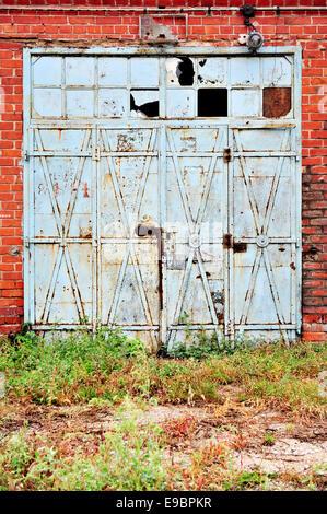Vieilles et rouillées portail en fer bleu à partir d'un entrepôt de la brique abandonnés Banque D'Images
