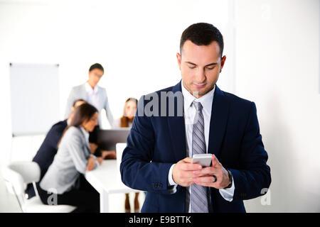 Businessman using smartphone en face de réunion d'affaires Banque D'Images