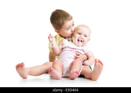 Frère d'amour embrassant bébé soeur isolated on white Banque D'Images
