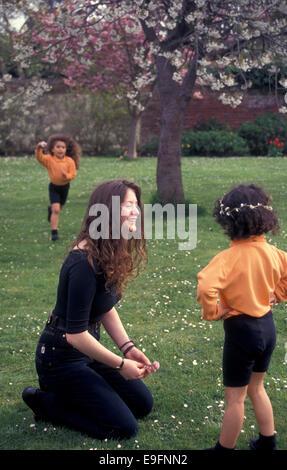 Assistante maternelle jouer avec deux filles dans le jardin Banque D'Images