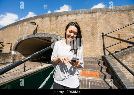 Smiling young woman using smart phone on stairs Banque D'Images