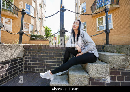 Full Length portrait of young woman sitting on stairs contre le bâtiment Banque D'Images