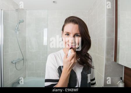 Portrait of young woman applying lipstick dans la salle de bains Banque D'Images