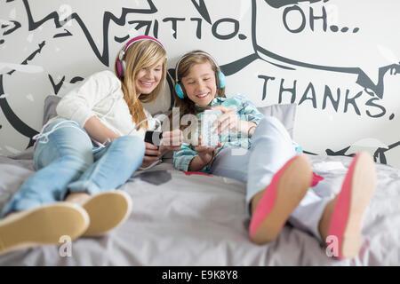 Sœurs détendue l'écoute de musique à la maison Banque D'Images