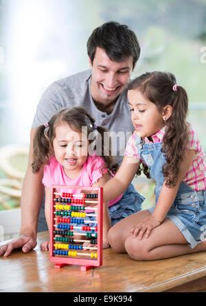Heureux père et filles jouant avec abacus dans chambre