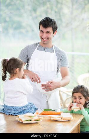 Heureux père de préparer les aliments avec peu de filles à la maison Banque D'Images