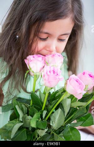 Cute girl smelling roses à la maison Banque D'Images