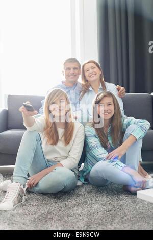 Famille de quatre heureux ensemble à la maison à regarder la télévision Banque D'Images