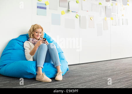 Smiling businesswoman using mobile phone on fauteuil poire in creative office Banque D'Images