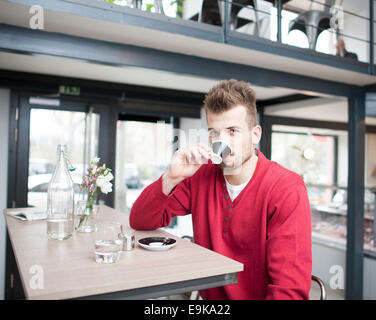 Portrait of young man drinking espresso in cafe Banque D'Images