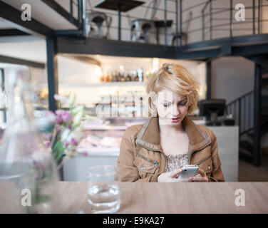 Inquiets young woman reading text message on cell phone in cafe