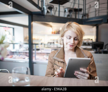 Beau young woman using digital tablet in cafe Banque D'Images