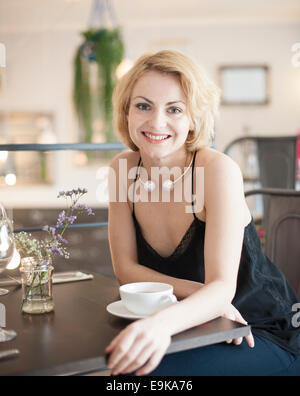 Portrait of happy young woman sitting at table Banque D'Images