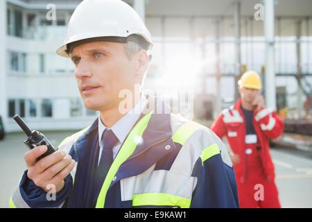 Travailleur à l'aide de talkie-walkie avec collègue en arrière-plan à cour d'expédition Banque D'Images
