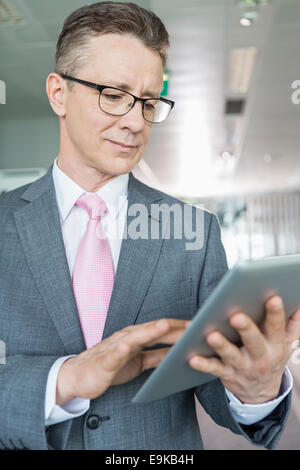 Middle-aged businessman using tablet PC in office Banque D'Images