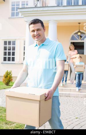 Portrait of man carrying cardboard box alors qu'un déménagement de la famille avec en arrière-plan Banque D'Images