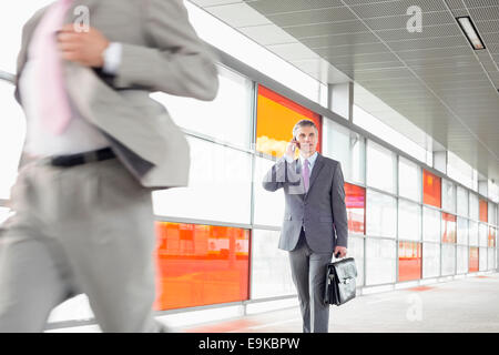 Middle aged businessman on call en marchant dans railroad station Banque D'Images