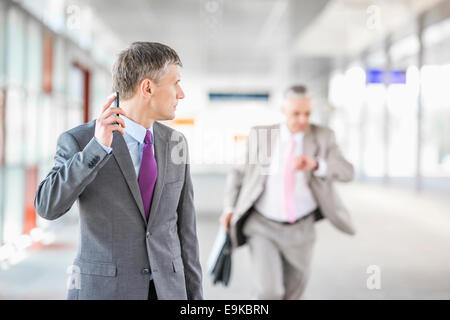 Middle aged businessman looking at collègue fonctionnant en railroad station Banque D'Images