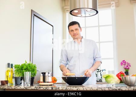 Portrait de l'homme confiant la préparation des aliments dans la cuisine Banque D'Images