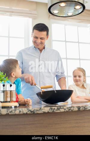 Homme heureux avec des enfants à la préparation des repas dans la cuisine Banque D'Images