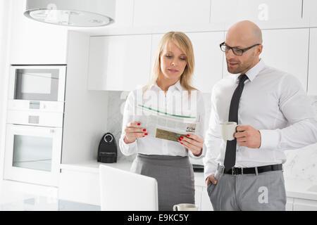 Mid adult woman reading newspaper tandis que le café dans la cuisine Banque D'Images