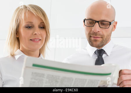Mid adult woman reading newspaper in kitchen Banque D'Images