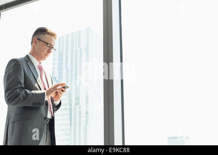 Mature businessman using cell phone by window Banque D'Images