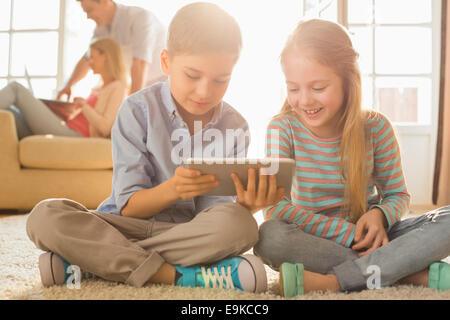 Frères et sœurs heureux using digital tablet sur le plancher avec les parents en arrière-plan Banque D'Images