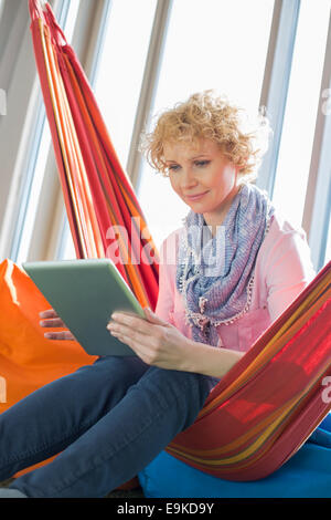 Creative businesswoman using digital tablet on hammock in office Banque D'Images