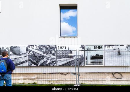 Man looking at photos affichées sur le mur, Mur de Berlin Memorial Park, Bernauer Strasse, Mitte, Berlin Banque D'Images