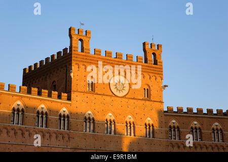 Sienne, Toscane, Italie. Façade du Palazzo Pubblico (Palazzo Comunale) éclairés par le soleil couchant, la Piazza del Campo.