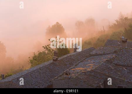 Rocca Ripesena, Ombrie, Italie. Vue sur les toits du village de mist-enveloppé valley, à l'aube. Banque D'Images