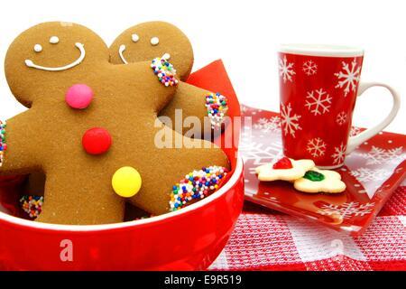 Les hommes d'épices dans un bol avec les cookies et festive mug en arrière-plan Banque D'Images