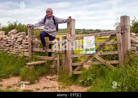 Une femelle walker l'ascension d'une stile sur le South West Coast Path à West Hill dans le Dorset, Angleterre, Banque D'Images