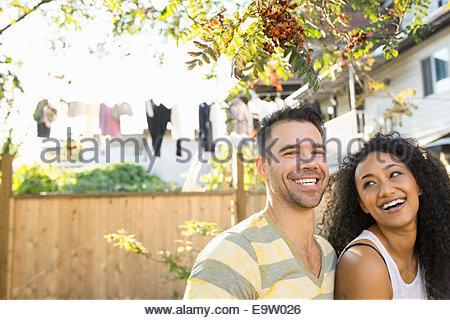 Portrait of laughing couple en arrière-cour ensoleillée Banque D'Images