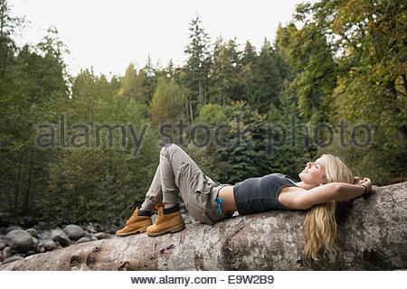 Jeune femme portant sur l'arbre tombé dans la région de Woods Banque D'Images
