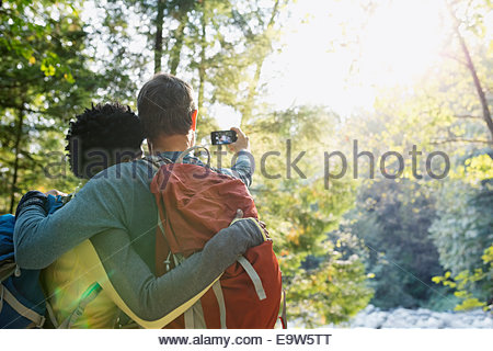 Couple qui en selfies sunny woods Banque D'Images