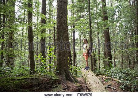 Portrait de jeune fille sur arbre tombé dans la région de Woods Banque D'Images
