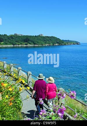Un couple en train de marcher le long du bord de mer à Falmouth en Cornouailles, Royaume-Uni Banque D'Images
