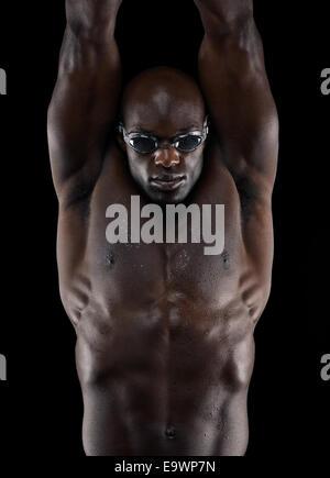 Studio shot of nageur professionnel formation sur fond noir. Les jeunes athlètes africains avec des lunettes de Banque D'Images
