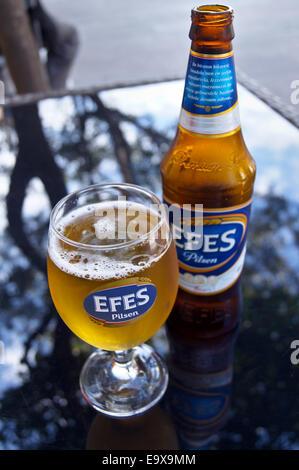 Un verre et une bouteille de bière turque de la FEAS, Bodrum, Turquie, verres de boissons table pub Banque D'Images