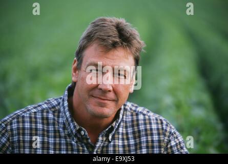 Agriculture - Portrait d'un agriculteur avec son domaine de croissance moyenne dans l'arrière-plan de soja / Minnesota, Banque D'Images