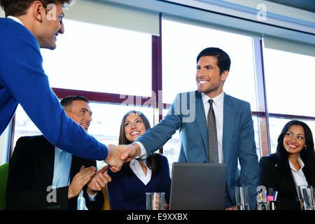 Les gens assis à la table tandis que deux d'entre eux shaking hands Banque D'Images