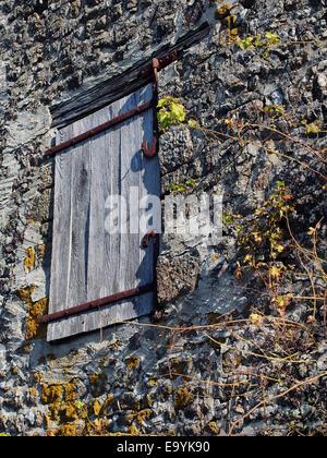 Vieille porte en bois sur charnières en fer dans le grenier à foin d'une ancienne grange en pierre dans le sud de Banque D'Images